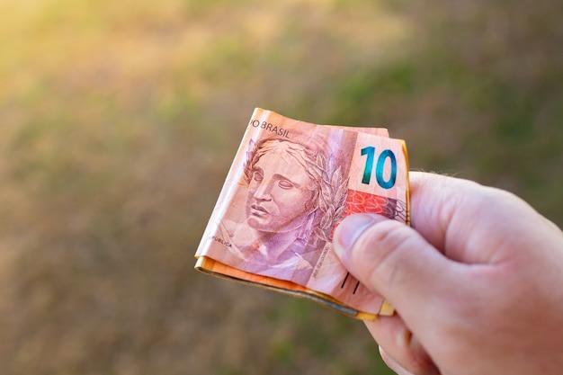 Een man met braziliaanse real-biljetten in zijn hand die gevouwen zijn