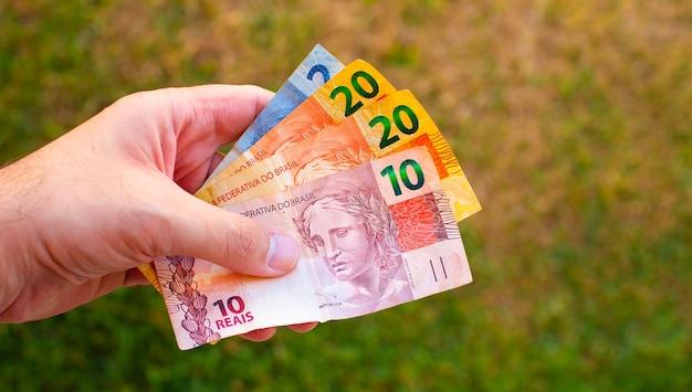 Een man met braziliaanse real-biljetten