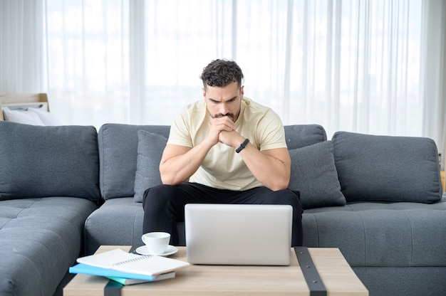 Een man met casual kleding die vanuit huis werkt, online vergadert, videogesprek voert, conferenties houdt en online met stressvol leert