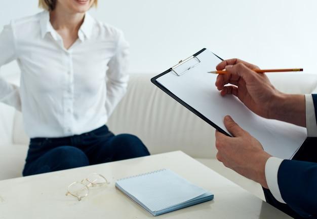 Een man met documenten en een vrouw op de bank aan tafel