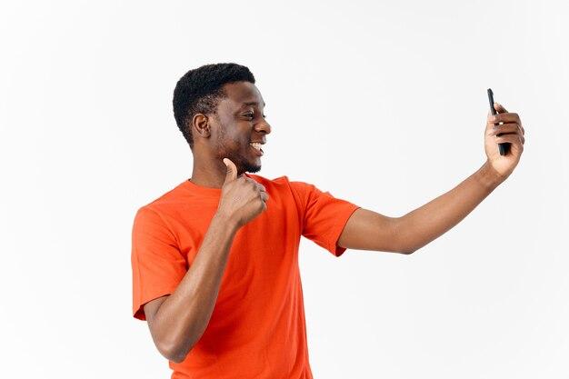 Een man met een afrikaans uiterlijk en in een oranje t-shirt laat zijn duim zien en kijkt naar een mobiele telefoon