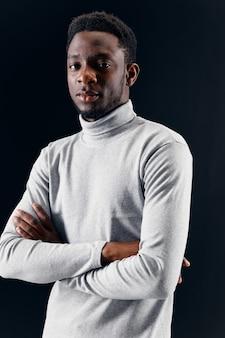 Een man met een afrikaans uiterlijk in een grijze trui op een donkere achtergrond