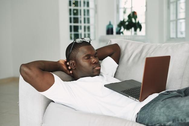 Een man met een afrikaans uiterlijk met een laptop ligt op de banksteun