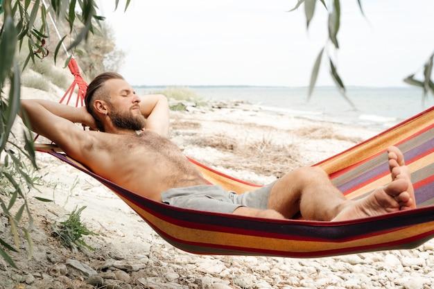 Een man met een baard aan de kust in een hangmat rust