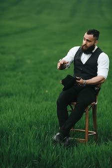 Een man met een baard, denkend in een veld bij een stoel