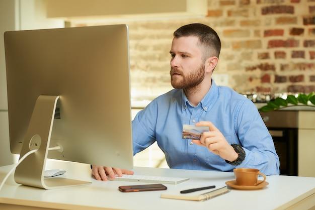 Een man met een baard denkt na over winkelen en typt thuis creditcardgegevens in een online winkel