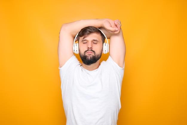 Een man met een baard die een witte koptelefoon draagt, zijn ogen sluit en naar rustige muziek luistert, zijn handen achter zijn hoofd gooit.