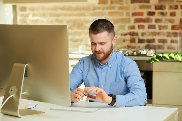 Een man met een baard die over online winkelen denkt terwijl thuis het houden van een creditcard in zijn handen