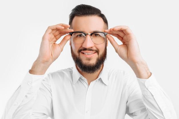 Een man met een baard en een bril, op een witte muur, lacht zwaar