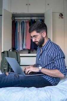 Een man met een baard en een gestreept overhemd in bed in zijn slaapkamer met behulp van een laptop
