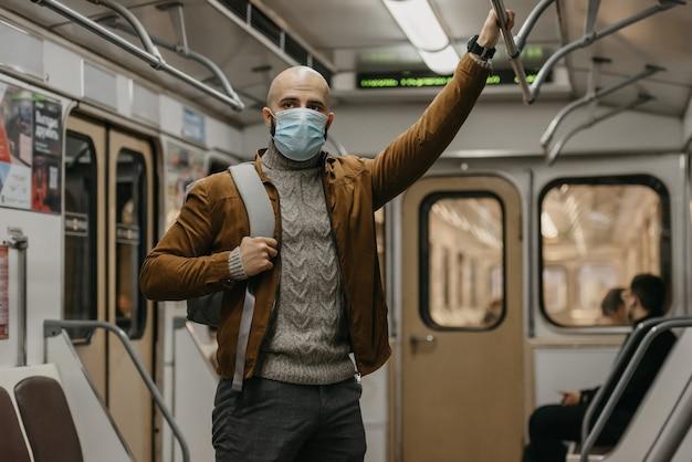 Een man met een baard en een medisch masker op zijn gezicht om verspreiding van het coronavirus te voorkomen, rijdt in een metro. een kale man met een chirurgisch gezichtsmasker tegen covid-19 staat op een metro.