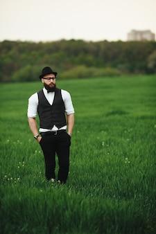 Een man met een baard en zonnebril die op het veld loopt