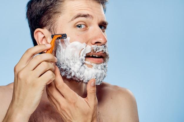 Een man met een baard heeft een scheermes in zijn handen, schoonheidsbehandelingen, kapperszaak thuis