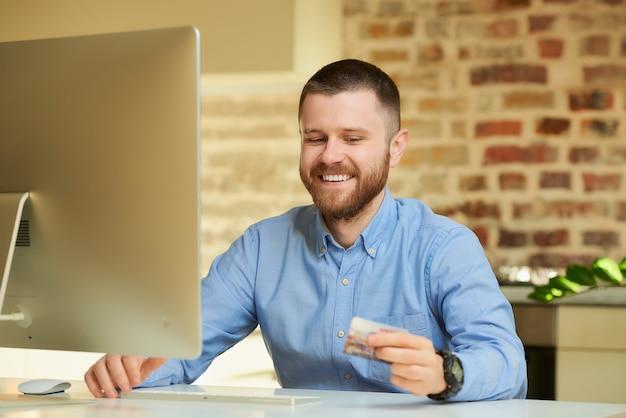 Een man met een baard in een blauw overhemd glimlacht thuis kijkend naar zijn creditcard in zijn handen