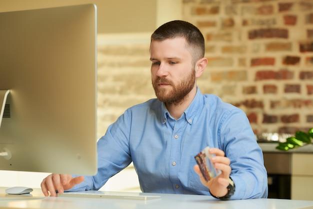Een man met een baard in een blauw shirt denkt aan online winkelen terwijl hij thuis een creditcard in zijn handen heeft
