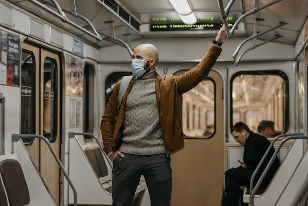 Een man met een baard in een gezichtsmasker om verspreiding van het coronavirus te voorkomen, houdt zich vast aan de leuning in het midden van een metro. een man met een chirurgisch masker tegen covid-19 staat op een metro.