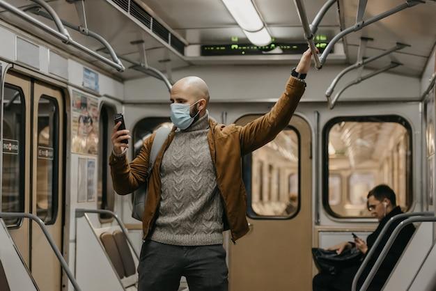 Een man met een baard in een medisch gezichtsmasker om verspreiding van het coronavirus te voorkomen, gebruikt een smartphone in een metro. een kale man met een chirurgisch masker tegen covid-19 houdt een mobiel vast in een metro