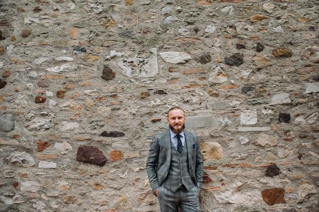 Een man met een baard in een streng grijs driedelig pak met stropdas in het oude centrum van sirmione, een stijlvolle man in een grijs pak in italië.