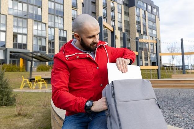 Een man met een baard in vrijetijdskleding haalt een computer uit zijn rugzak om op afstand te werken. concept van buitenshuis werken