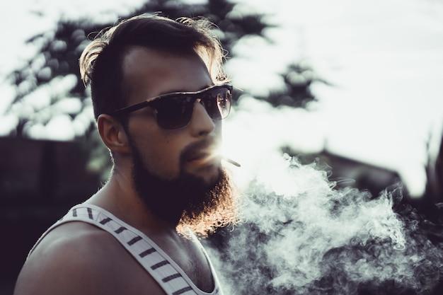 Een man met een baard in zonnebril rookt een sigaret bij zonsondergang, laat een dikke tabaksrook vrij
