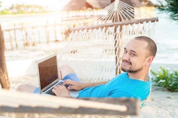 Een man met een baard liggend in een hangmat met een laptop