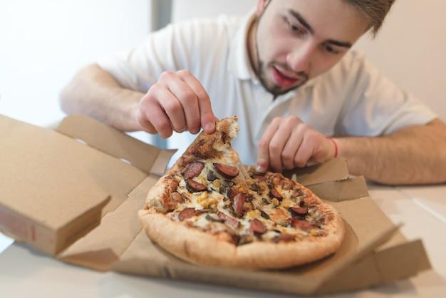 Een man met een baard pakt een heerlijk stuk pizza uit een kartonnen doos en kijkt haar hongerig aan.