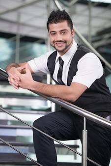 Een man met een baard staat op de trap en glimlacht.