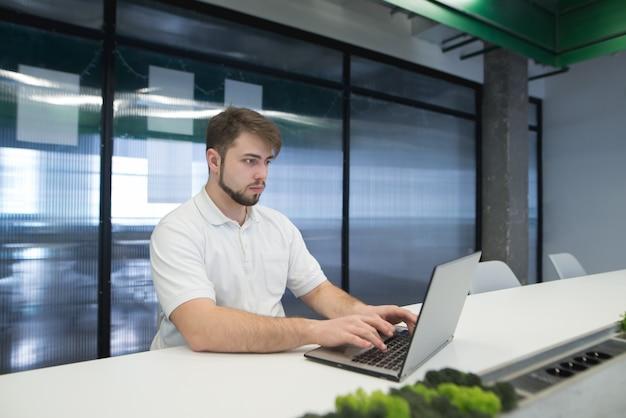 Een man met een baard werkt op een laptop op kantoor.