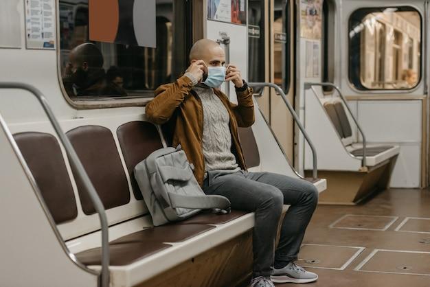 Een man met een baard zet een medisch masker op zijn gezicht om de verspreiding van het coronavirus in een metroauto te voorkomen. een kale man met een chirurgisch gezichtsmasker tegen covid-19 zit in een metro.