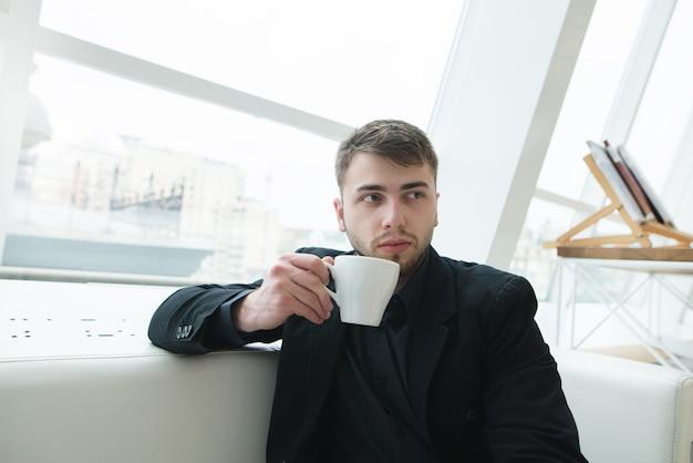 Een man met een baard zit op een mooi licht café met een kopje koffie in zijn handen. koffiepauze in het restaurant.