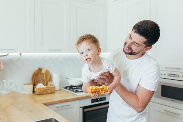 Een man met een babyjongen maakt ontbijt klaar, een vader en een zoon