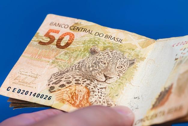Een man met een bankbiljet van 50 braziliaanse real in close-up foto met blauwe achtergrond