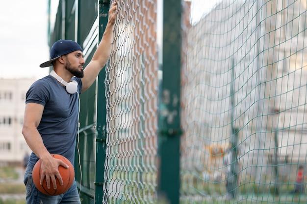 Een man met een basketbal kijkt overdag achter een hek op straat uit