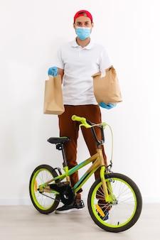 Een man met een beschermend masker bezorgt voedsel op een fiets. online winkelen en express levering. quarantaine