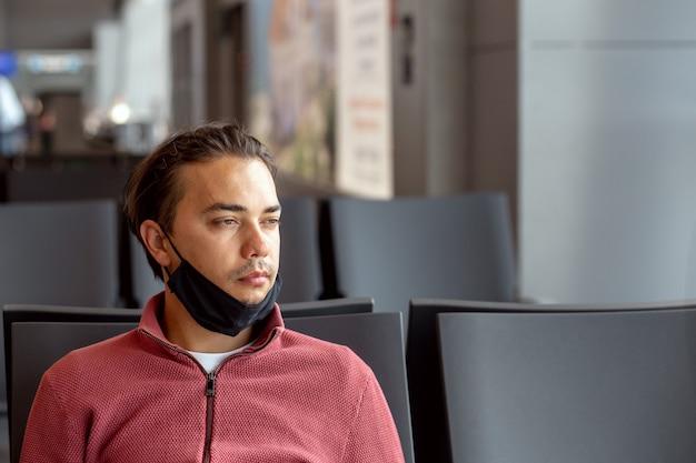 Een man met een beschermend zwart medisch masker op het gezicht op de luchthaven wacht op de vlucht