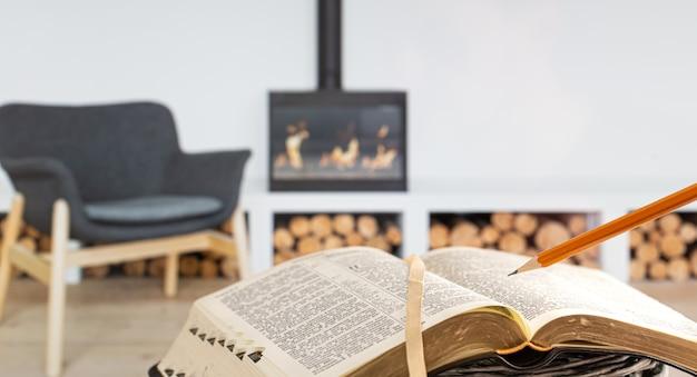 Een man met een bijbel met een potlood, tegen de achtergrond van de woonkamer met een open haard. een boek lezen in een gezellige omgeving.