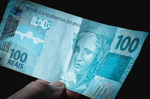 Een man met een biljet van 100 braziliaans geld, de braziliaanse real op zwarte achtergrond