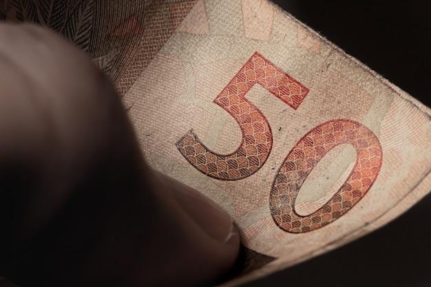 Een man met een biljet van 50 reais van de braziliaanse real in macrofotografie
