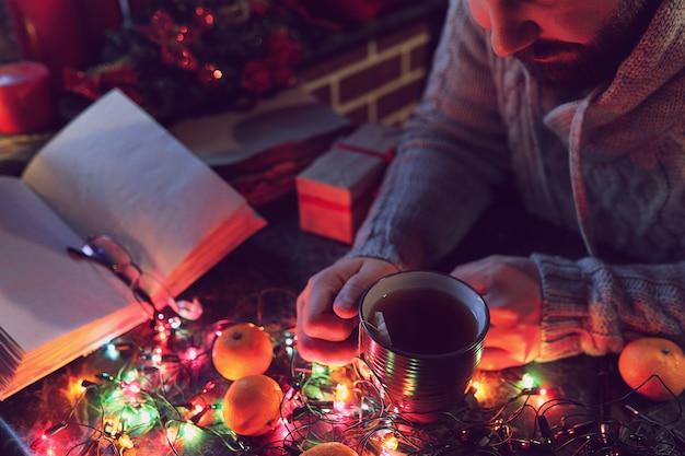 Een man met een blanco boek in zijn handen voor de nieuwjaarstafel met versieringen