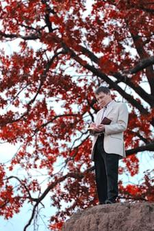 Een man met een boek in zijn handen staat van een boom met rode bladeren