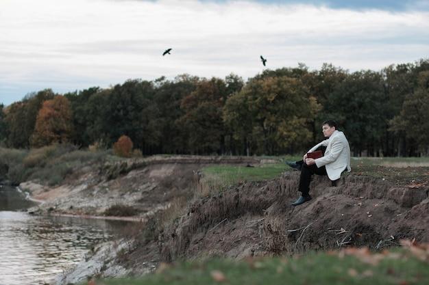 Een man met een boek in zijn handen zit nadenkend op de rand van een klif