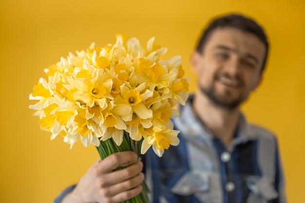 Een man met een boeket bloemen op een gekleurde muur.