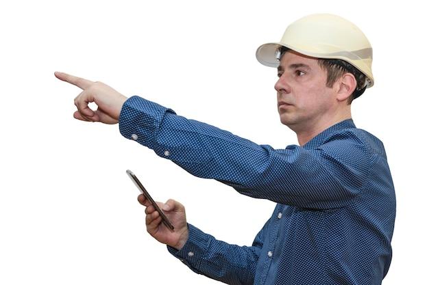 Een man met een bouwhelm op een witte geïsoleerde muur met een telefoon wijst zijn hand in de verte. de voorman. bouwer. ingenieur.