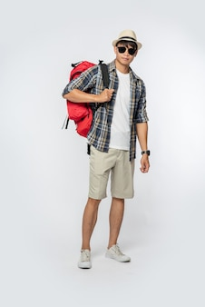 Een man met een bril gaat op reis, draagt een hoed en draagt een rugzak