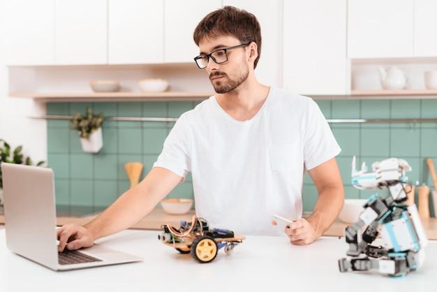 Een man met een bril is bezig met het programmeren van een robot.