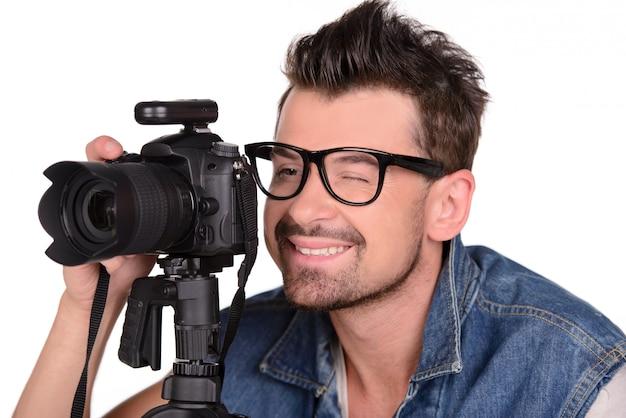 Een man met een bril maakt een foto in de studio