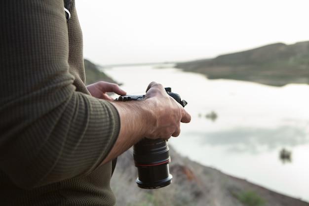 Een man met een camera staat 's avonds aan het meer