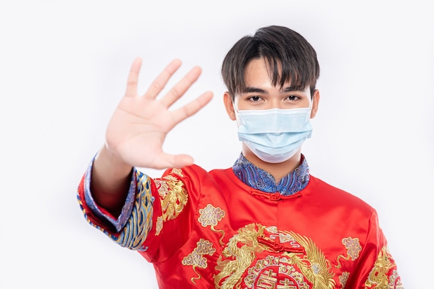 Een man met een cheongsam en een masker laat zien dat mensen die geen maskers dragen tijdens het nieuwe maanjaar niet kunnen winkelen.