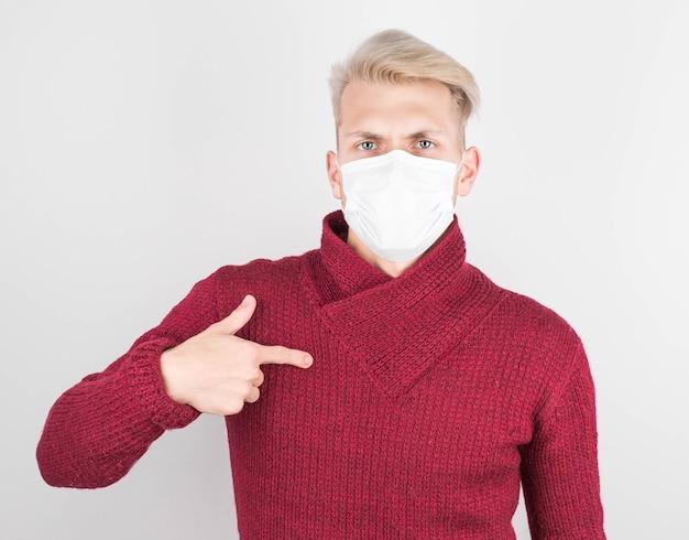 Een man met een chirurgisch masker en een rode trui wijst naar zichzelf en draagt een beschermend filter om besmetting met het coronavirus te voorkomen