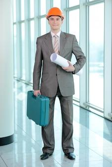 Een man met een diplomaat staat en kijkt naar de camera